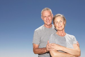 Mature Couple in gray tshirts smiling at camera
